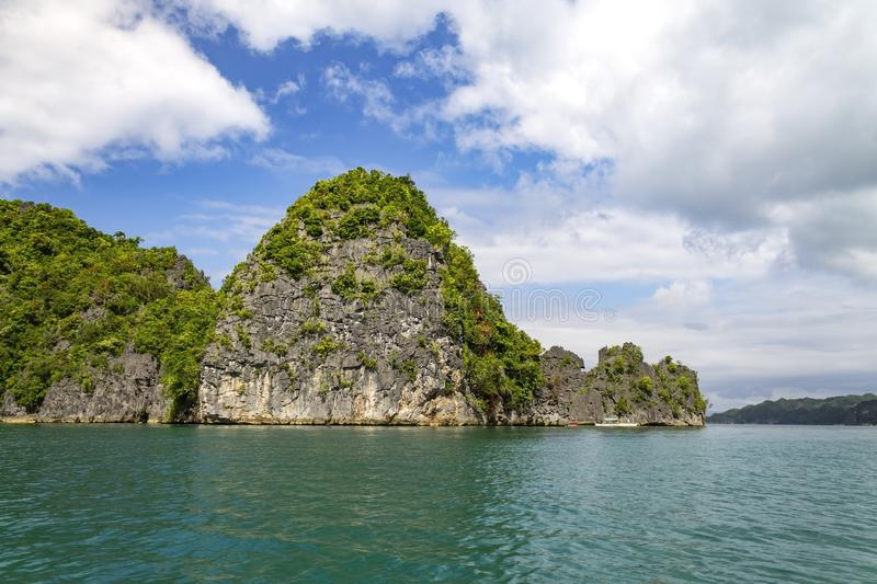 Limestone cliff on Lahus Island beach, Caramoan, Camarines Sur Province, Luzon in the Philippines. Limestone cliff with banca boats on Lahus Island beach in the royalty free stock photo