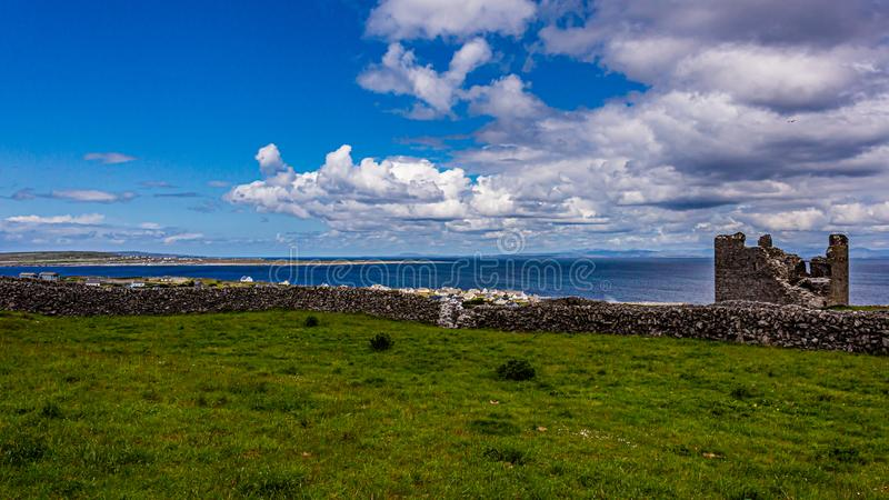 Limestone fence on Inis Oirr island with the ruined castle tower, the village and the Atlantic Ocean in the background. Limestone fence on Inis Oirr island with stock photo