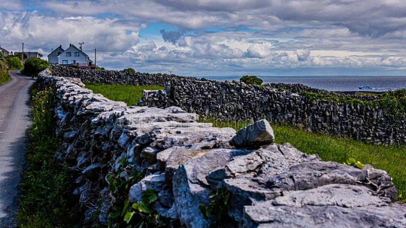 Limestone fences beside a rural road on Inis Oirr Island with houses and the sea in the background. Wonderful sunny day on Inisheer Island, Aran Islands royalty free stock photos