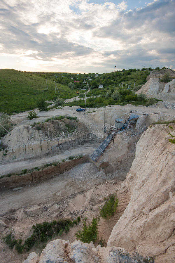 Limestone - gravel extraction. Crushing mini-factory escalator in the quarry of limestone rock, landscape seen from behind, Moldova and village. Mining lime stock image