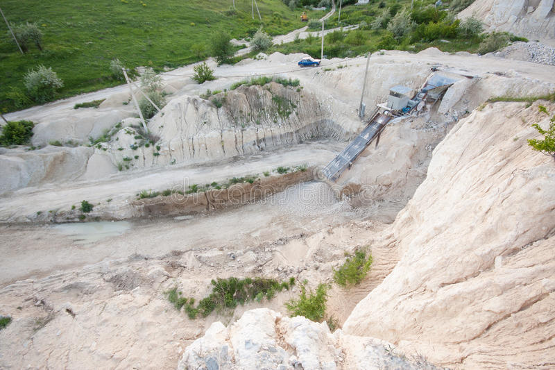 Limestone - gravel extraction. Crushing mini-factory escalator in the quarry of limestone rock, Moldova. Mining lime brick and gravel royalty free stock photo