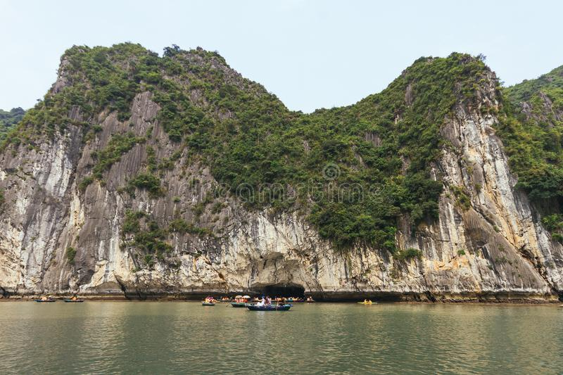 Limestone island over emerald water with growing green trees on it with tourist rowing boat below in summer at Halong Bay. royalty free stock photo