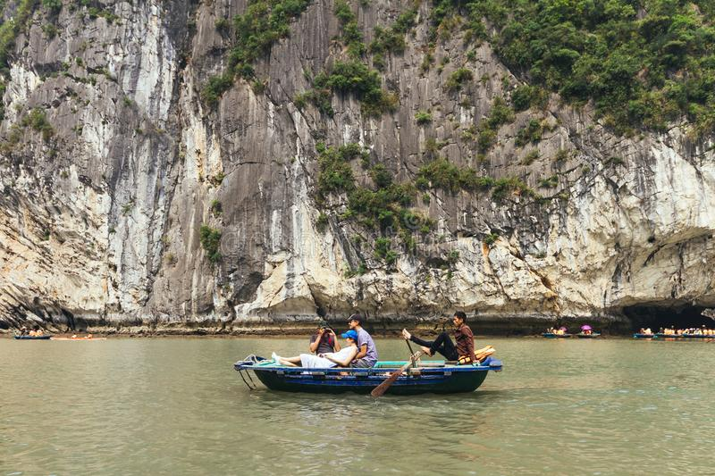 Limestone island over emerald water with growing green trees on it with tourist rowing boat below in summer at Halong Bay. stock image