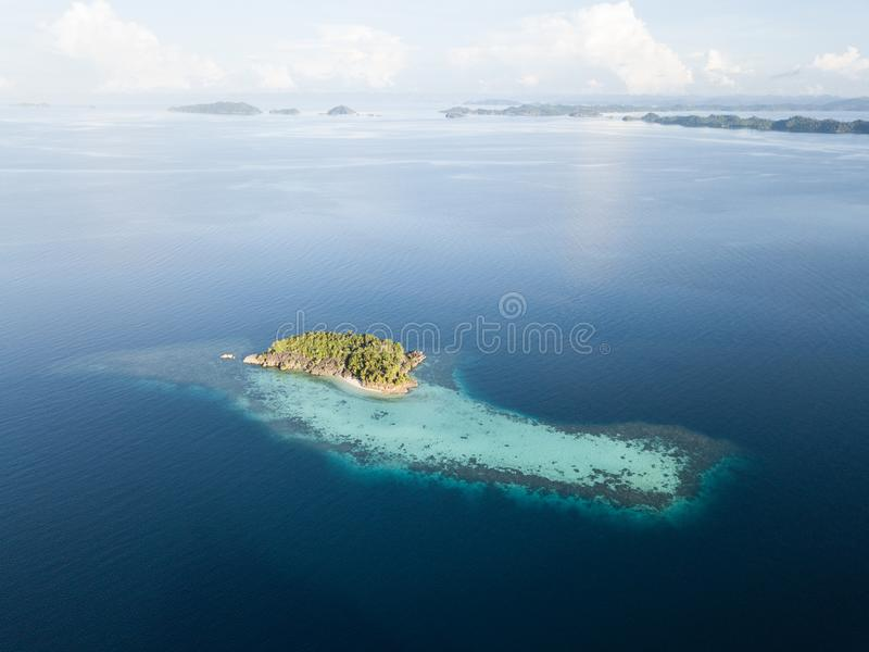 Limestone Island and Reef Aerial in Raja Ampat. The limestone islands found in Raja Ampat rise from calm, blue seas in a remote part of eastern Indonesia. This stock photo