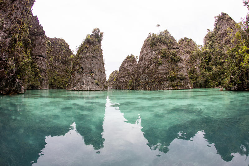Limestone Island and Tropical Lagoon in Raja Ampat. Rugged limestone islands rise around a peaceful lagoon in Raja Ampat, Indonesia. This remote region is known stock photo