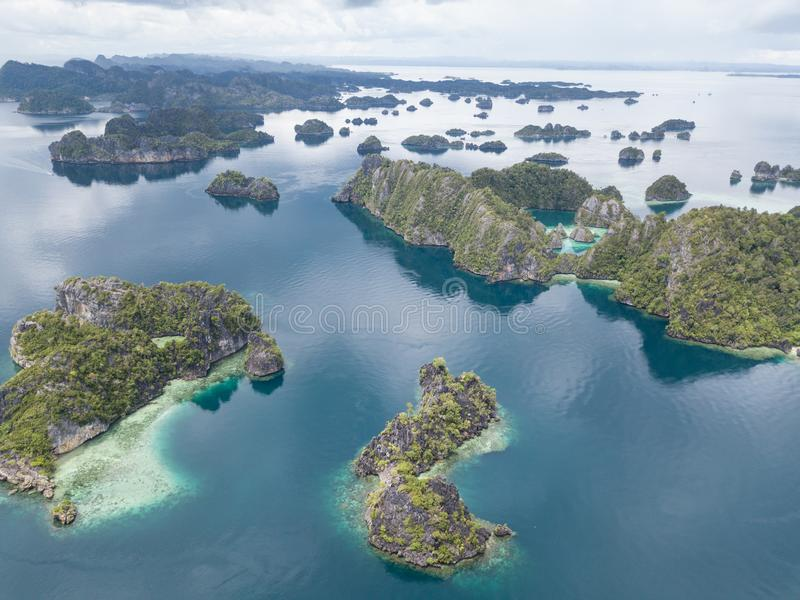Limestone Islands Aerial in Raja Ampat, Indonesia. The limestone islands found in Raja Ampat rise from calm, blue seas in a remote part of eastern Indonesia stock image