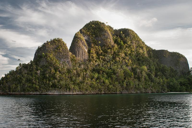 Limestone Islands and Lagoon in Raja Ampat. Rugged limestone islands tower over a beautiful, tropical lagoon in Raja Ampat, Indonesia. This remote region is stock photos