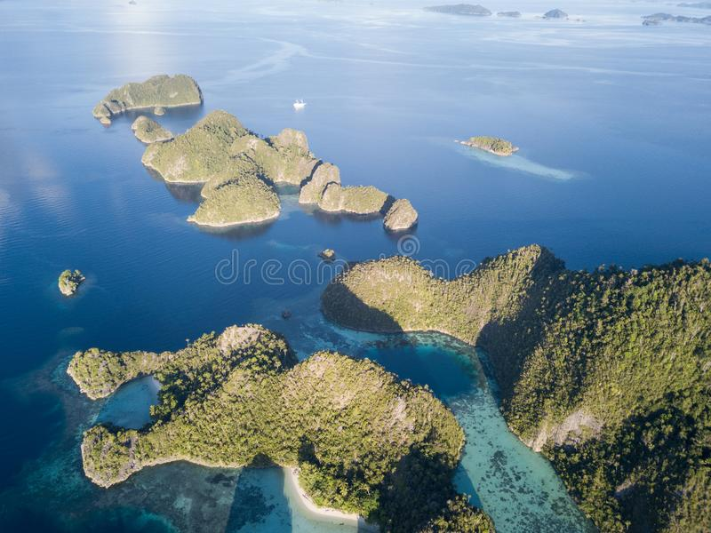 Aerial of Calm Seas and Rock Islands in Raja Ampat. The limestone islands of Misool, Raja Ampat are surrounded by healthy, shallow coral reefs. This remote stock images
