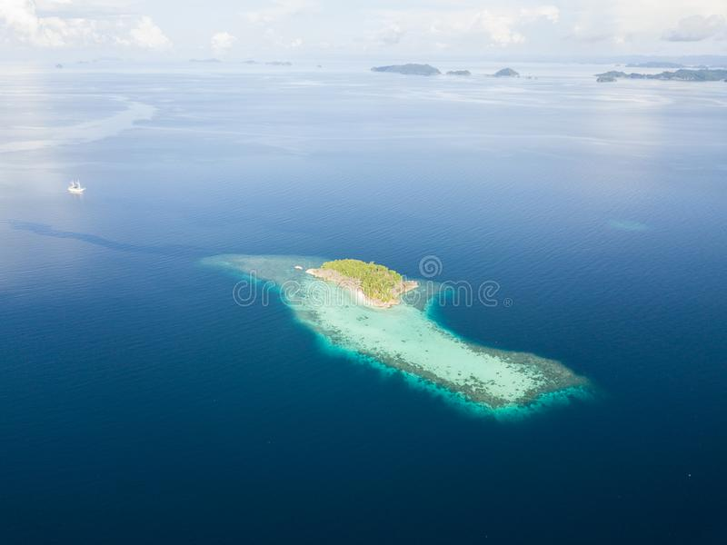 Aerial of Remote Island in Raja Ampat. The limestone islands of Raja Ampat are surrounded by healthy, shallow coral reefs. This remote region in eastern stock image