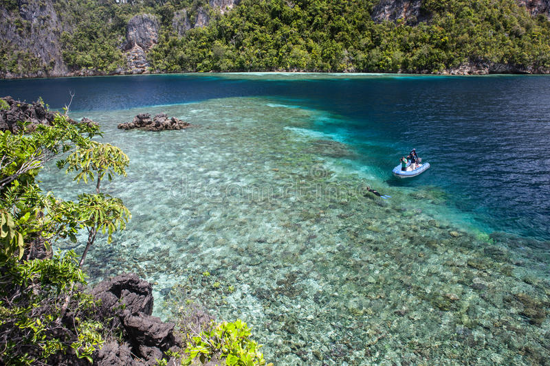 Limestone Islands and Reef in Raja Ampat. A remote lagoon is surrounded by limestone islands in Raja Ampat, Indonesia. This region is within the Coral Triangle stock photo