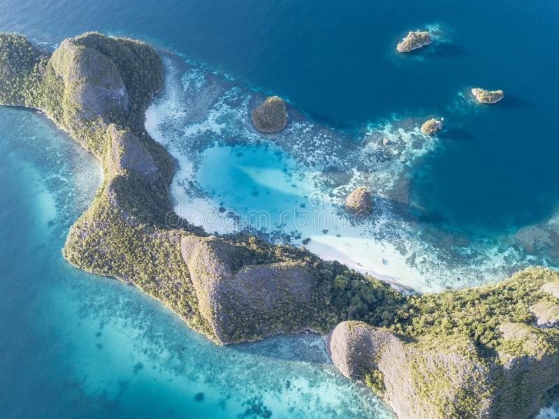 Aerial View of Limestone Islands in Raja Ampat. Limestone islands rise from a gorgeous lagoon in Wayag, Raja Ampat, Indonesia. This remote, tropical region is royalty free stock photo