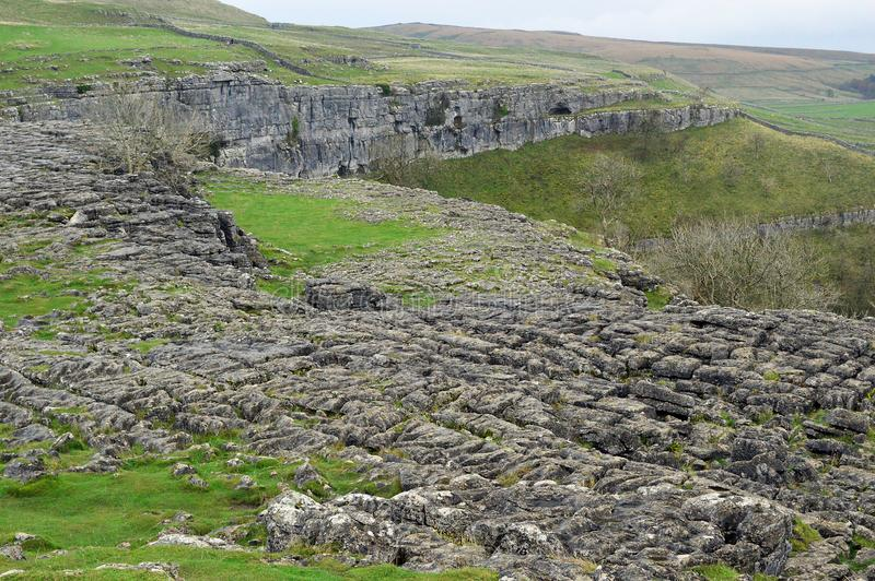 Limestone pavement above malham cove yorkshire uk. A limestone pavement is a natural karst landform consisting of a flat, incised surface of exposed limestone royalty free stock photo