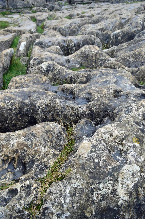 Limestone pavement above malham cove yorkshire uk. A limestone pavement is a natural karst landform consisting of a flat, incised surface of exposed limestone royalty free stock photos
