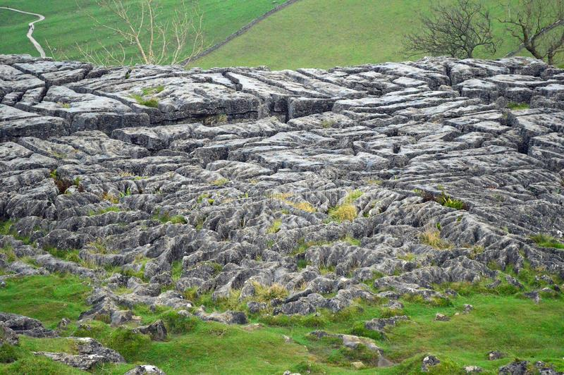 Limestone pavement above malham cove yorkshire uk. A limestone pavement is a natural karst landform consisting of a flat, incised surface of exposed limestone stock photo
