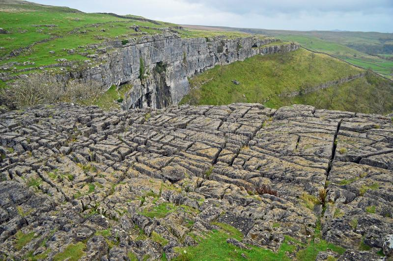 Limestone pavement above malham cove yorkshire uk. A limestone pavement is a natural karst landform consisting of a flat, incised surface of exposed limestone royalty free stock image