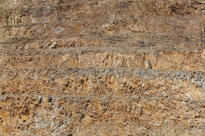 Limestone quarry vertical wall. Rocky substrate by levels. Horizontal stock photography