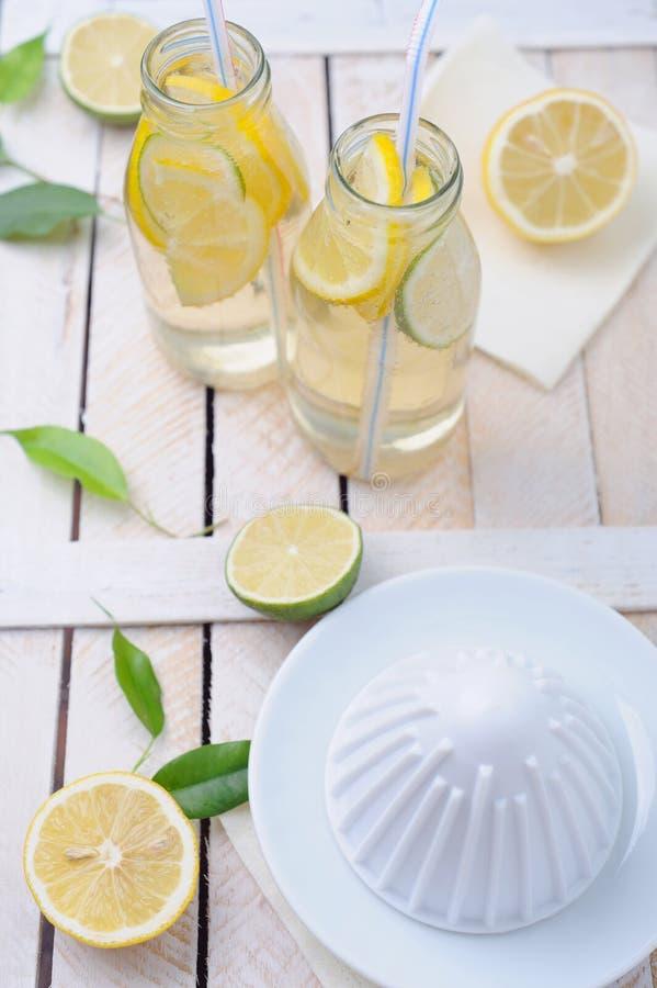 Limetta e limone fresco, spremitoio e due vetri di limonata sulla tavola immagini stock libere da diritti