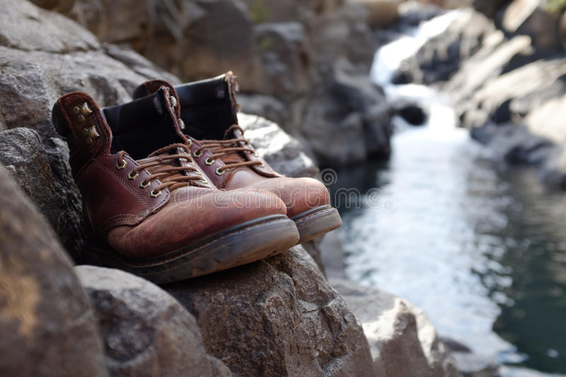 Limited focus old hiking boots in front of waterfall royalty free stock image