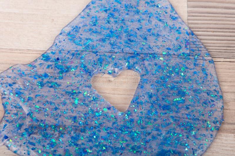Limo azul do brilho com um furo da forma do coração em uma tabela fotos de stock royalty free