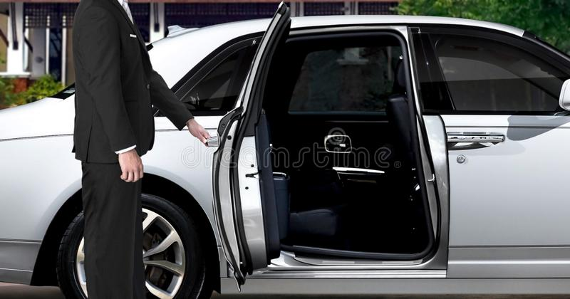 Limo driver opening white car door royalty free stock images