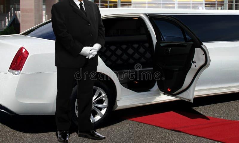 Limo kierowcy pozycja obok rozpiecz?towanego samochodowego drzwi z czerwonym chodnikiem zdjęcia stock