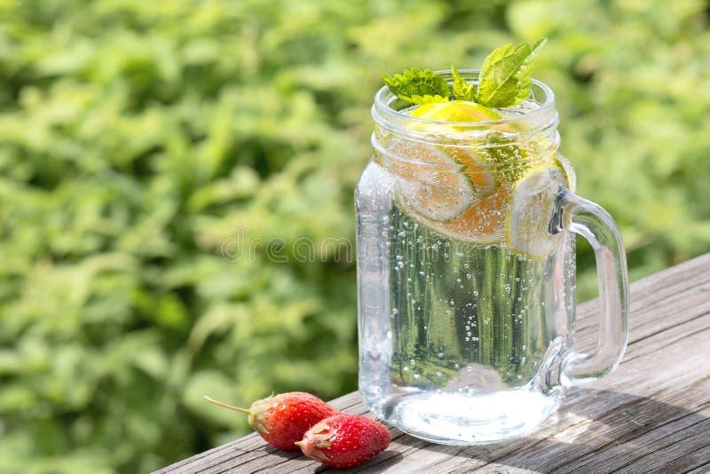 Limonada com um cal e uma hortelã em um frasco de vidro em uma tabela de madeira velha Grama verde no fundo Bebida do ver?o fotografia de stock royalty free