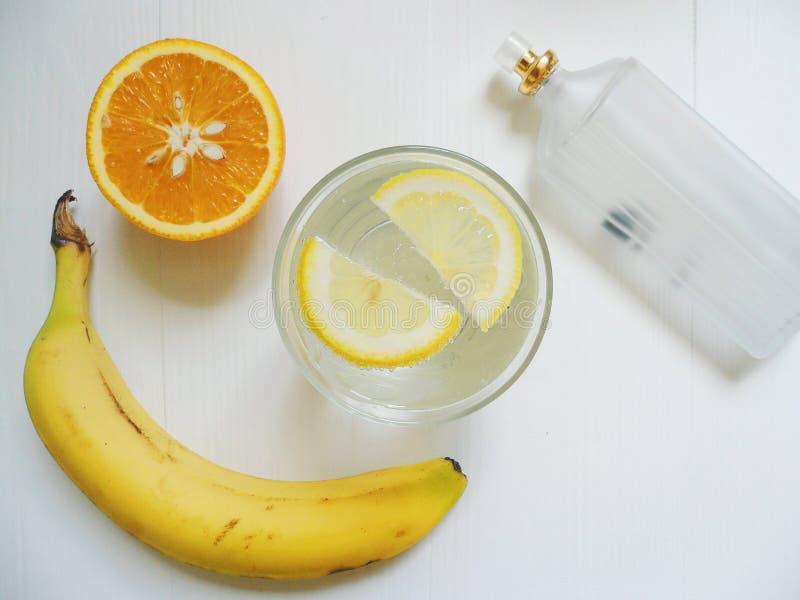 limonada con el limón, la naranja, el plátano y eau de toilette en el fondo blanco fotografía de archivo libre de regalías