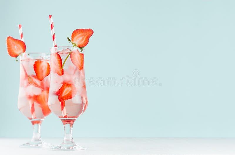Limonada cor-de-rosa da morango com água mineral, fatias do fruto, cubos de gelo, palha no vidro misted na tabela de madeira bran foto de stock