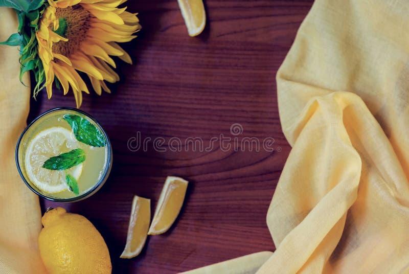 Limonada da hortelã com fatias do limão em um fundo de madeira com um girassol bonito, ainda fotografia da vida fotografia de stock