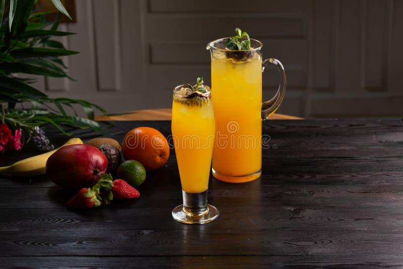 Limonada da manga - fruto de paixão em um jarro e um vidro e um fruto em um fundo de madeira foto de stock royalty free