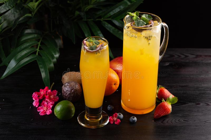 Limonada da manga - fruto de paix?o em um jarro e um vidro e um fruto em um fundo de madeira imagem de stock