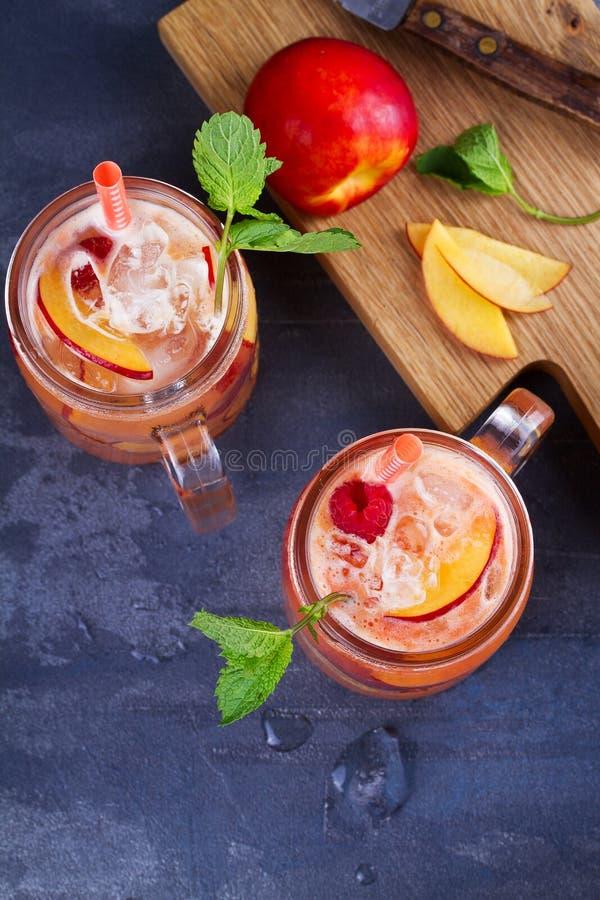 Limonada de la frambuesa del melocotón, adornada con la menta Fruta Berry Cocktail en tarros fotos de archivo