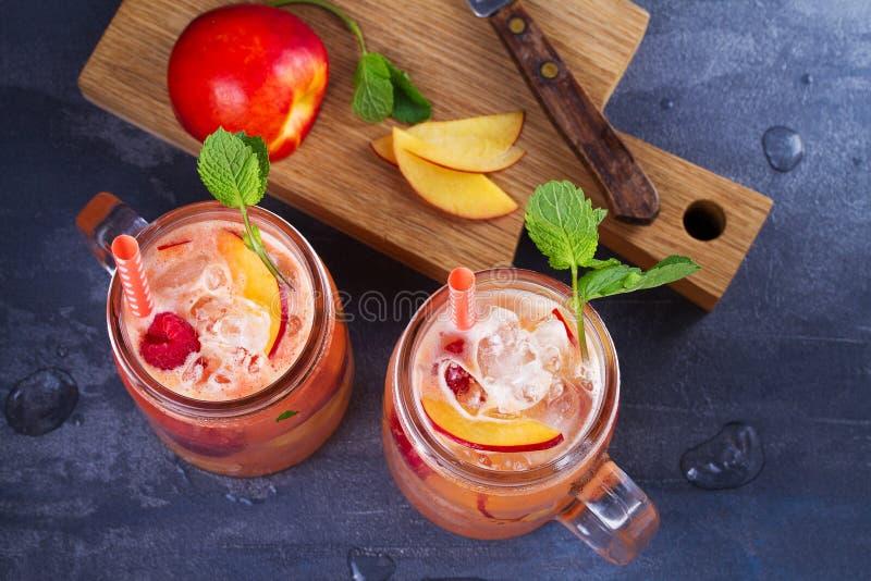 Limonada de la frambuesa del melocotón, adornada con la menta Fruta Berry Cocktail en tarros fotografía de archivo libre de regalías