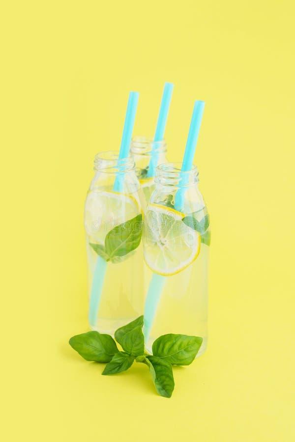 Limonada en las botellas de cristal con la paja en fondo amarillo brillante imagen de archivo