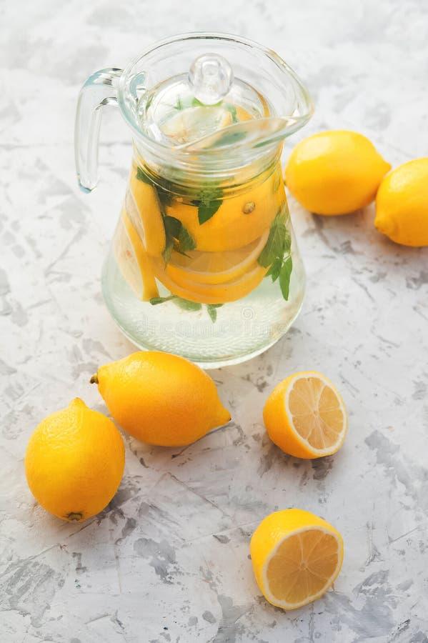 Limonada en un jarro transparente Limones, menta, vidrios, jarra en un fondo imagenes de archivo