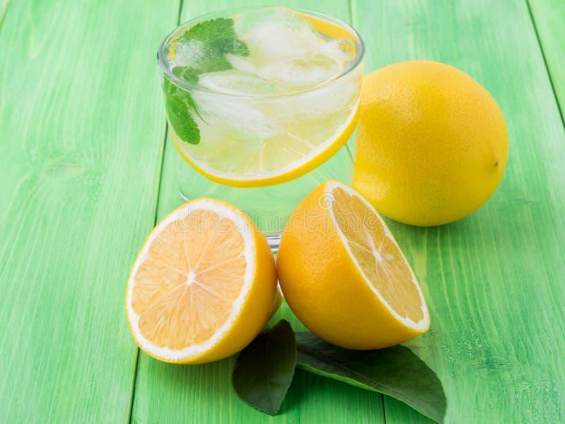 Limonada en un vidrio, un limón medio, hojas frescas en la etiqueta verde foto de archivo libre de regalías
