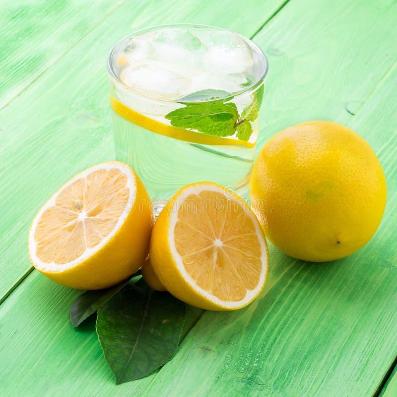 Limonada en un vidrio, un limón medio, hojas frescas en la etiqueta verde imagen de archivo libre de regalías