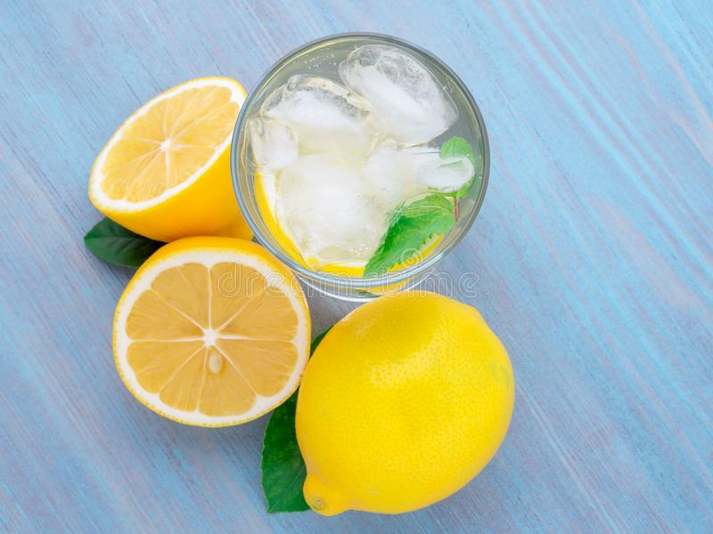 Limonada en un vidrio, un limón medio, hojas frescas en la madera azul foto de archivo libre de regalías