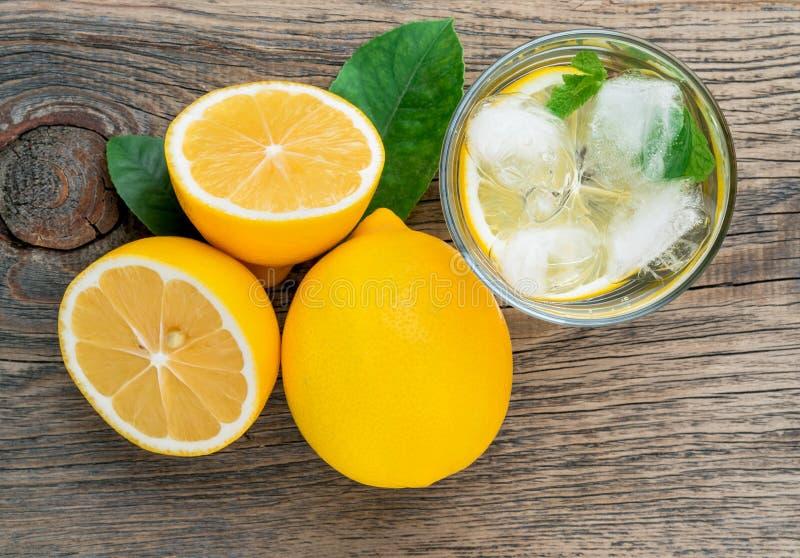 Limonada en un vidrio, un limón medio, hojas frescas en viejo t de madera foto de archivo libre de regalías