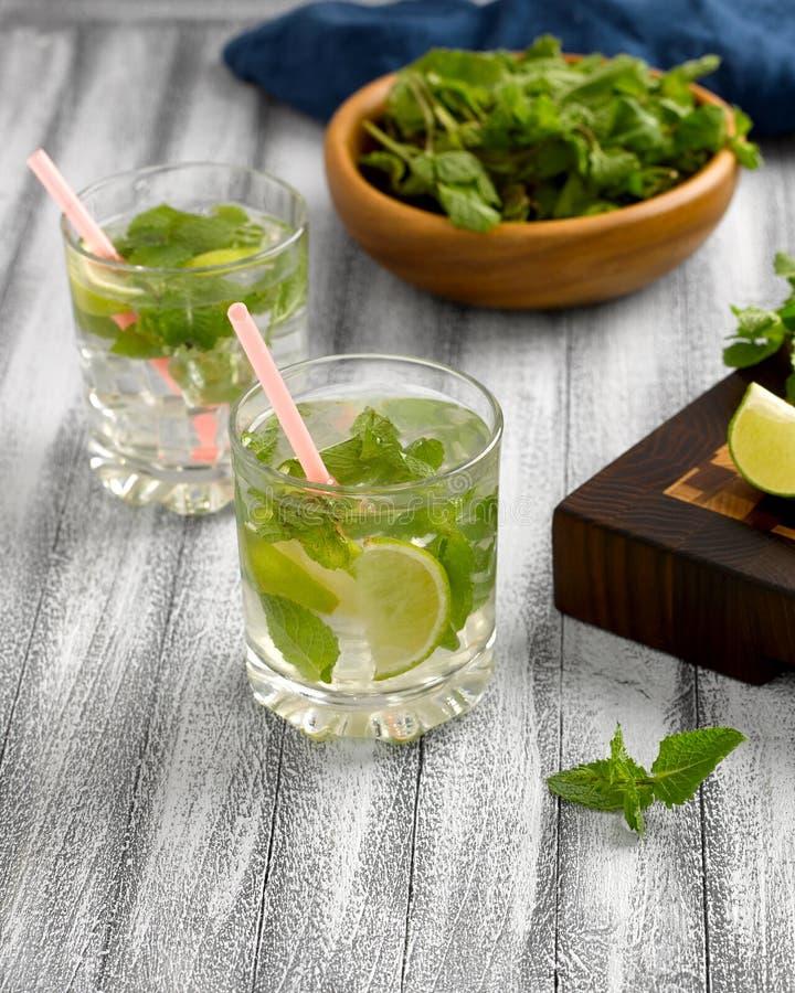 Limonada fresca con la menta y cal e hielo en las tazas de cristal imagenes de archivo