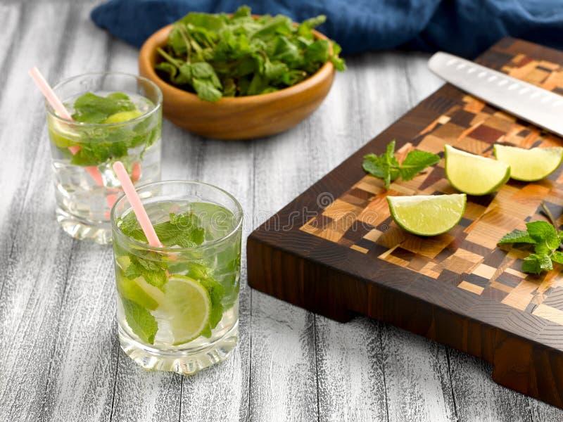 Limonada fresca con la menta y cal e hielo en las tazas de cristal fotografía de archivo libre de regalías
