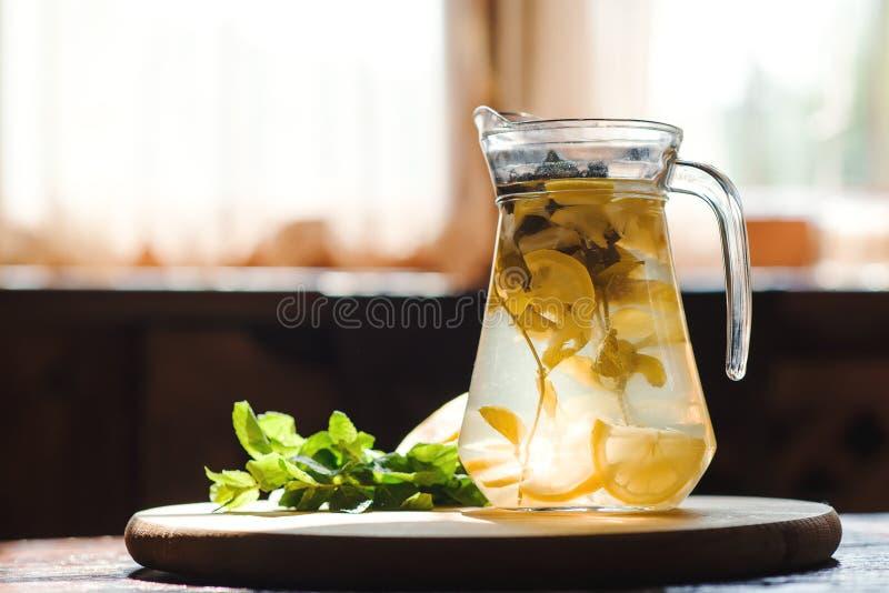 Limonada fresca en tarro con el limón y la menta amarillos en fondo de madera de la cocina Detox del agua imagen de archivo