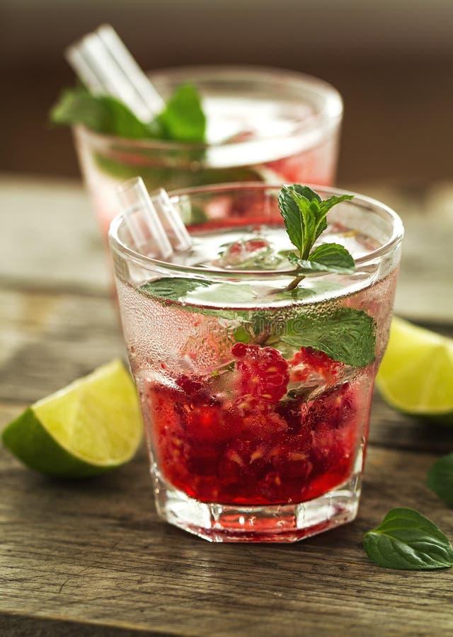 Limonada fresca fría sabrosa de la bebida con la frambuesa, la menta, el hielo y el li foto de archivo
