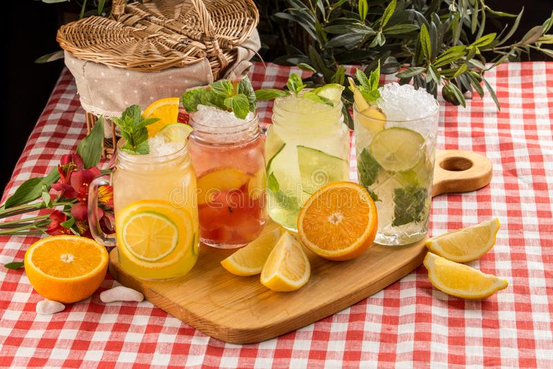 Limonada fria ajustada com limão, laranja e pêssego na placa de madeira no guardanapo de matéria têxtil imagens de stock royalty free