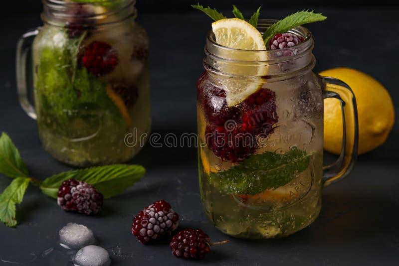 Limonada hecha en casa con el limón, la zarzamora y la menta en el vidrio contra un fondo oscuro, foto horizontal imagen de archivo libre de regalías