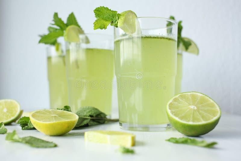 Limonada hecha en casa fresca con el limón, la cal y la menta en un vidrio en el fondo blanco e ingredientes que ponen en la tabl foto de archivo libre de regalías