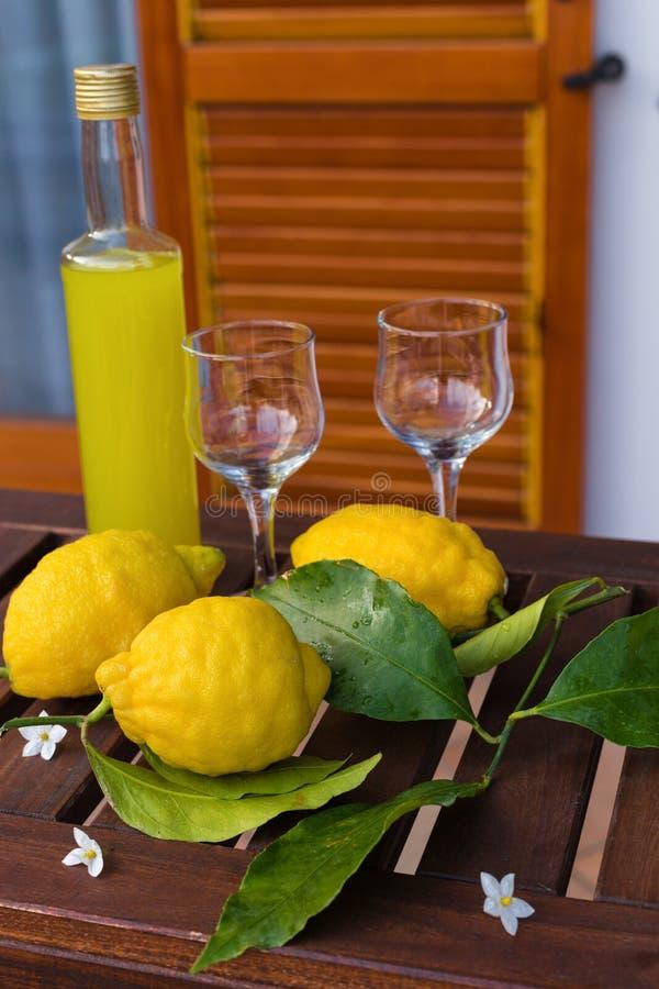 Limonada ou limoncello em uma garrafa de vidro, vidros, limões com folhas em uma tabela do serviço no terraço fotos de stock royalty free