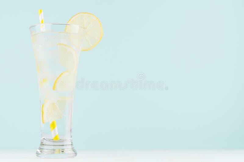 Limonada transparente da dieta caseiro com limão, cubos de gelo, soda, palha listrada amarela no vidro misted na tabela de madeir fotos de stock royalty free