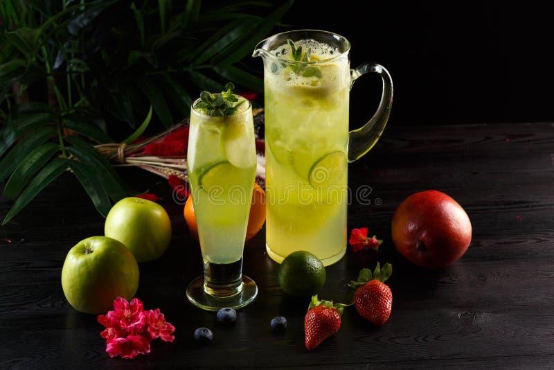 Limonada verde de la manzana con la cal en un jarro y un vidrio y frutas en un fondo oscuro imagenes de archivo