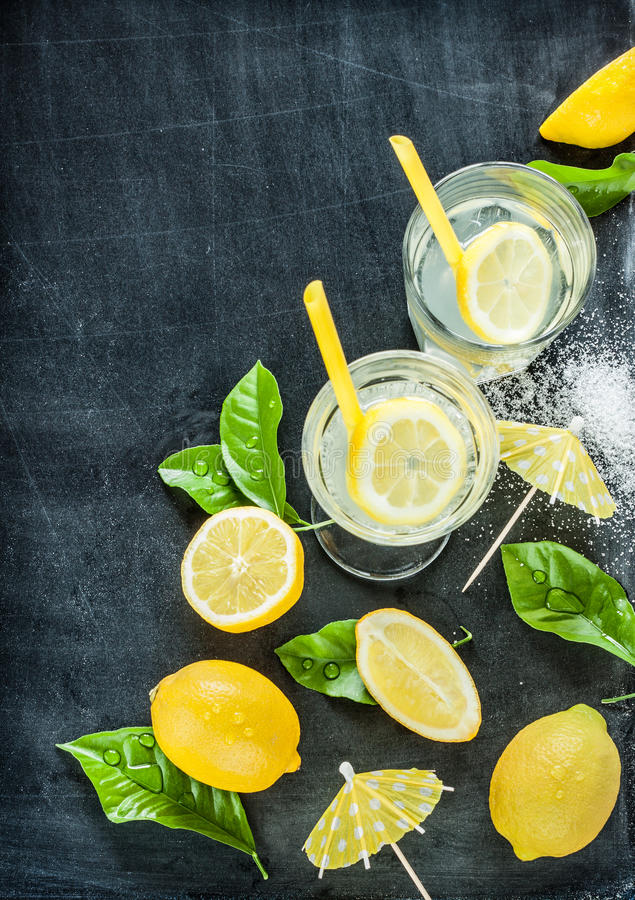Limonade, citrons, feuilles sur le tableau noir images stock
